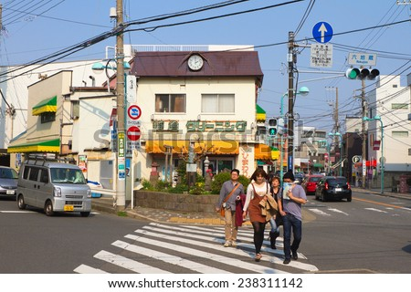 KAMAKURA, JAPAN - MARCH 10: People are crossing the street on March 10, 2013 in Kamakura, Japan. It is a popular tourist destination in Kanagawa Prefecture, 50 kilometers south-south-west of Tokyo. - stock photo