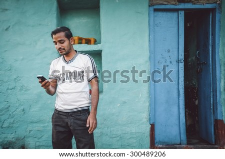 KAMALAPURAM, INDIA - 02 FABRUARY 2015: Indian man looks at his mobile phone outside his home. Post-processed with grain, texture and colour effect. - stock photo