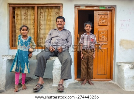 KAMALAPURAM, INDIA - 02 FEBRUARY 2015: Father and his two children infront of their home in a town close to Hampi - stock photo