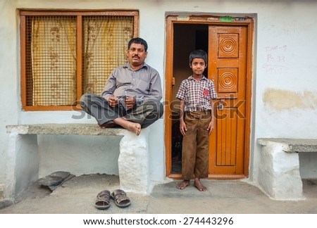 KAMALAPURAM, INDIA - 02 FEBRUARY 2015: Father and son ouside their home in a town close to Hampi - stock photo