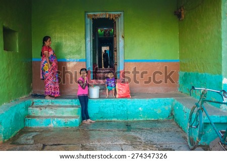 KAMALAPURAM, INDIA - 02 FEBRUARY 2015: Indian family outside their home in a town close to Hampi - stock photo