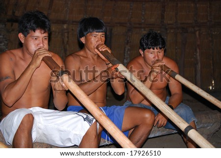 KAMAYURA VILLAGE, BRAZIL - MAY 18: Members of a threatened Indian tribe, the Kamayura, playing sacred flutes on May 18, 2008, in the Kamayura village. - stock photo