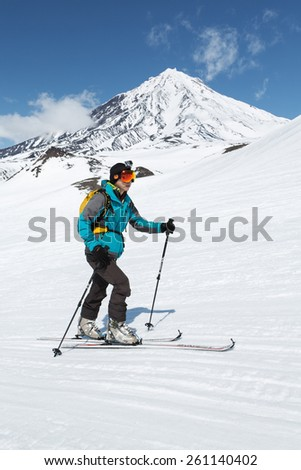 KAMCHATKA, RUSSIA - APRIL 26, 2014: Ski mountaineer climbs on skis on background active Koryaksky Volcano. Russia, Far East, Kamchatka Peninsula. - stock photo