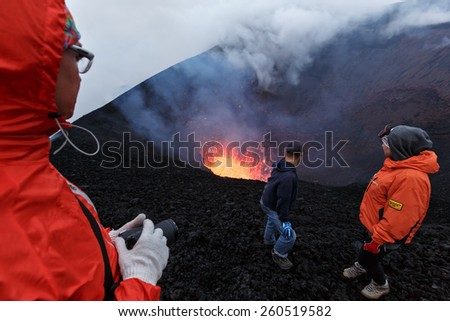 KAMCHATKA, RUSSIA - JULY 27, 2013: Eruption Tolbachik Volcano on Kamchatka, travelers watching the lava lake in the crater of the active volcano. Russia, Far East, Kamchatka Peninsula. - stock photo