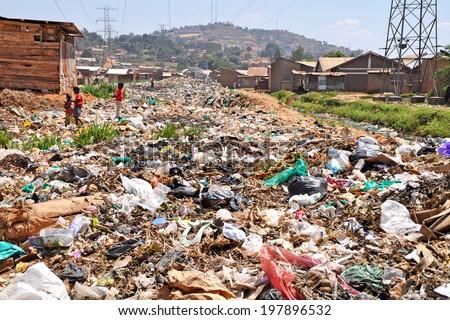 KAMPALA, UGANDA, AFRICA - CIRCA FEBRUARY 2009: Unidentified children in the garbage dump in the Kampala slums circa February 2009 in Uganda, Africa. Kampala is the largest city and capital of Uganda. - stock photo
