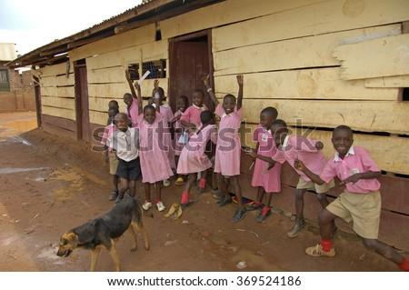 Kampala, Uganda-10 April 2017: Children in pink school uniform in front of their school waving. - stock photo