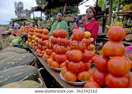 Kampala, Uganda-13 April 2017 Unidentified women sell vegetables on the road to Murchison Falls on December 9, 2007 near Masindi, Uganda. Selling farm products is only source money for them. - stock photo