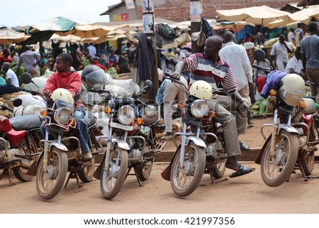 KAMPALA, UGANDA - CIRCA NOVEMBER 2015: Boda boda moto drivers waiting for clients on the roadside next to a busy local fruits and vegetables market. - stock photo