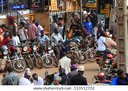 KAMPALA, UGANDA - SEPTEMBER 28, 2012.  Motorcycle taxis and drivers wait on the streets for passengers as people walk by in Kampala, Uganda on September 28,2012. - stock photo