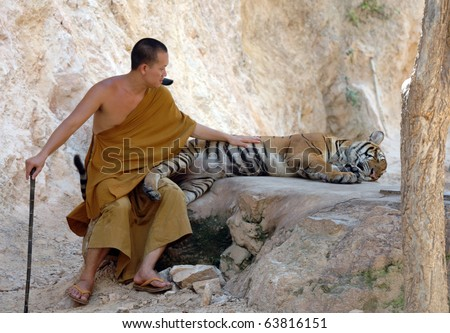 KANCHANABURI - APRIL 26: Buddhist monk with a bengal tiger on April 26 2007, Kanchanaburi, Thailand - stock photo