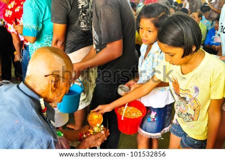 "KANCHANABURI,THAILAND - APRIL 13: Unidentified Thai people showering graybeard in ""Songkran Festival 2012(water festival)"" at temple on April 13,2012 in Kanchanaburi,Thailand - stock photo"