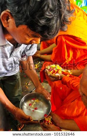 "KANCHANABURI,THAILAND - APRIL 13: Unidentified Thai people showering monk in ""Songkran Festival 2012(water festival)"" at temple on April 13,2012 in Kanchanaburi,Thailand - stock photo"