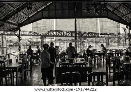 KANCHANABURI, THAILAND � FEBRUARY 2: Tourists enjoy a lunch break nearby the bridge on the river Kwai in Kanchanaburi, Thailand on February 2, 2009. The bridge is famous due to its history in WW2. - stock photo