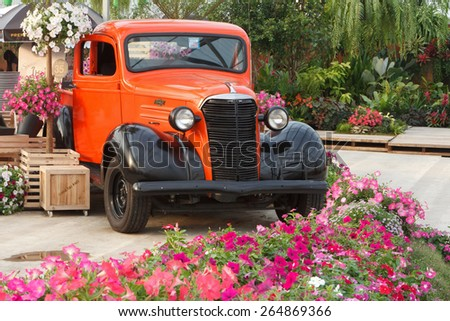 KANCHANABURI, THAILAND - JANUARY 9: Old American classic car parked in a garden decorated with flowers on January 9, 2015 in Kanchanaburi Thailand. - stock photo