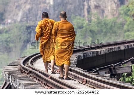 Kanchanaburi, Thailand - March 21: Unidentified monks waking on the Death Railway, Thailand-Burma railway on World War II March 21, 2015 - stock photo
