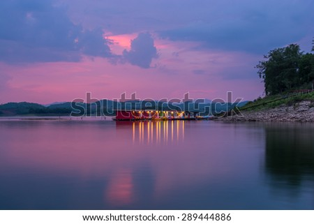 Kanchanaburi , Thailand - May 12,2015 : Sunset view at lake in the Srinakarin Dam with the Phupai colorful Resort with raft house  in Kanchanaburi, Thailand.