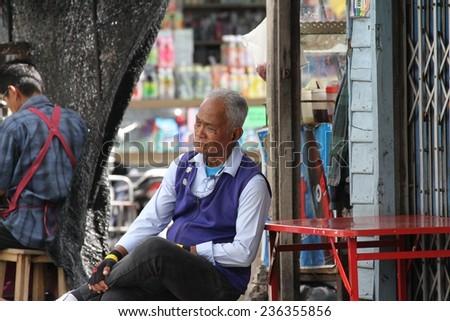 KANCHANABURI, THAILAND - SEPTEMBER 3: A closeup of an elderly local man sitting outside a shop in the town of Kanchanaburi, Thailand on the 3rd September, 2014. - stock photo