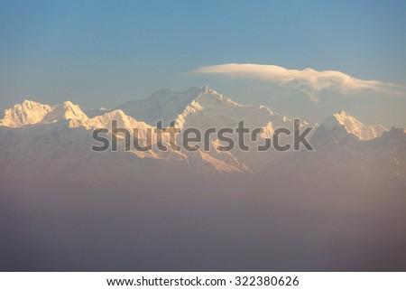 Kanchenjunga range peak in early morning light just after the sunrise through thick mist , Darjeeling, Sikkim, India - stock photo
