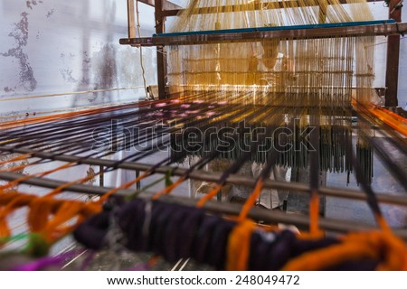 KANCHIPURAM, INDIA - SEPTEMBER 12, 2009: Man weaving silk sari on loom. Kanchipuram is famous for hand woven silk sarees and most of the city's workforce is involved in  weaving industry - stock photo