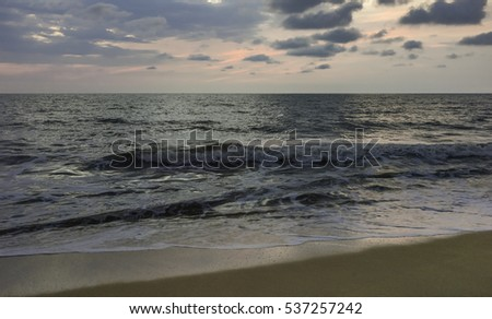 Kannur, Kerala, India. View from the sandy beach across the Arabian Sea at sunset on a serene evening at Thottada Village, near Kannur, Kerala, India.