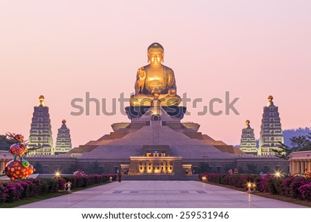 Kaohsiung, Taiwan - December 15, 2014: Sunset at Fo Guang Shan, the biggest buddist temple of Kaohsiung in Taiwan, with a buddhist monk walking by. - stock photo