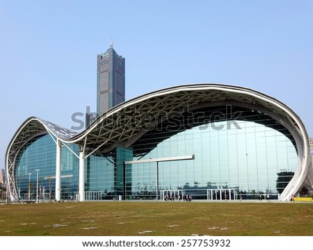 KAOHSIUNG, TAIWAN -- FEBRUARY 20, 2015: The new Kaohsiung Exhibition Center with its unique waveform roof. In the back is the 85 story Tuntex Tower, the highest building in the city. - stock photo