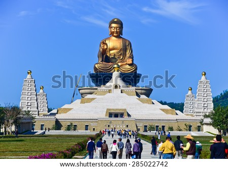 Kaohsiung, Taiwan - January 8, 2012 : People visiting a Chinese temple and a golden Buddha statue in Kaohsiung, Taiwan. - stock photo