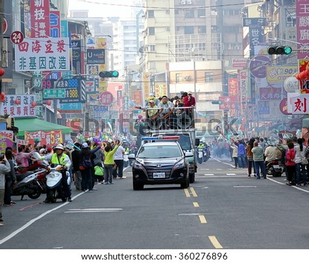 KAOHSIUNG, TAIWAN -- JANUARY 9, 2016: Supporters of DPP presidential candidate Tsai Ying-Wen welcome her motorcade with flags and firecrackers during a campaign event.