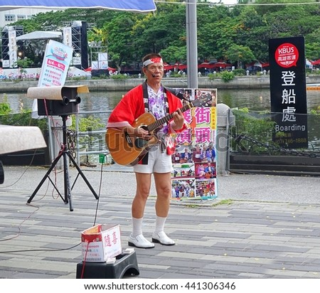 KAOHSIUNG, TAIWAN -- JUNE 9, 2016: A male busker wearing Japanese clothes performs popular Japanese songs on the banks of the Love River.