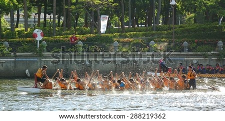 KAOHSIUNG, TAIWAN -- JUNE 14, 2015: An unidentified team of rowers trains for the upcoming Dragon Boat Races on the Love River. - stock photo