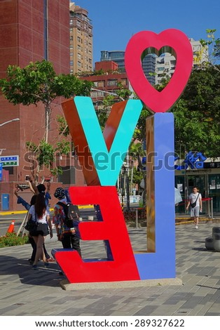 KAOHSIUNG, TAIWAN -- JUNE 14, 2015: Tourists take photos in front of a colorful Love sign on the banks of the Love River in Kaohsiung city.