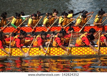 KAOHSIUNG, TAIWAN - JUNE 11: Two unidentified female teams compete in the 2013 Dragon Boat Races on the Love River on June 11, 2013 in Kaohsiung