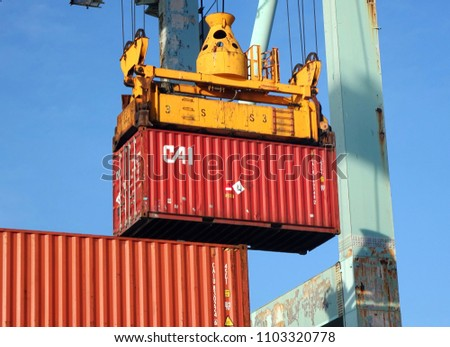 KAOHSIUNG, TAIWAN -- MAY 26, 2018: A shipping container is being loaded in the busy port of Kaohsiung, a major trading hub for Taiwan.