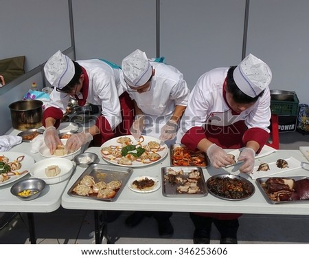 KAOHSIUNG, TAIWAN -- NOVEMBER 28, 2015: Three chefs prepare dishes for the cooking competition during the 2015 Hakka Food Festival, which is a yearly public outdoor event.