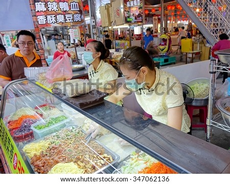KAOHSIUNG, TAIWAN -- NOVEMBER 20, 2015: Two female shop assistents prepare spring rolls  filled with tofu and vegetables at the Jiangguo Outdoor Market.