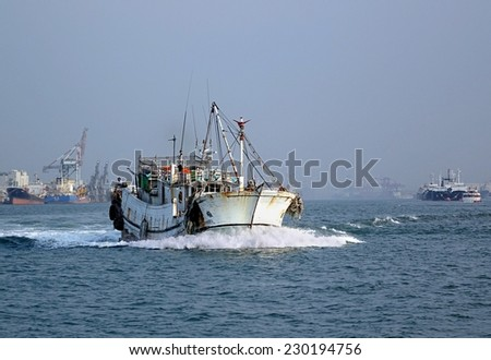 KAOHSIUNG, TAIWAN -- OCTOBER 11, 2014: A traditional Chinese fishing boat plows through waters of Kaohsiung harbor. - stock photo