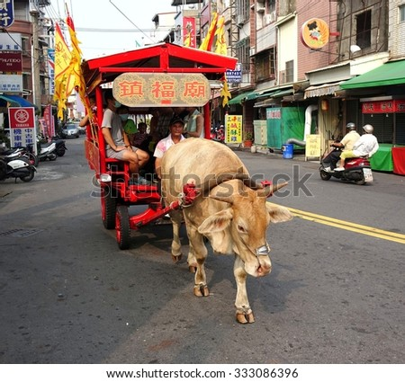 KAOHSIUNG, TAIWAN -- OCTOBER 17, 2015: A traditional ox cart transports tourists during the yearly Wannian Festival. - stock photo