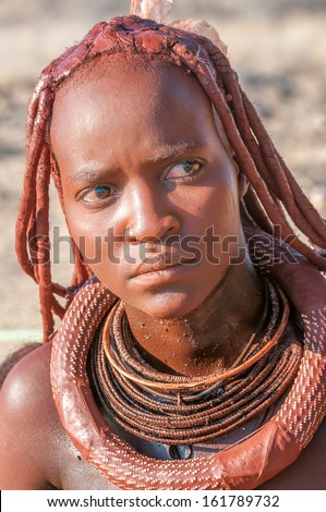 KAOKOLAND,NAMIBIA - OCTOBER 2,2012 - Himba woman decorated with products offered for sale.Women hair painted with a layer of clay loam.Himba is an ethnic group living in northern Namibia.