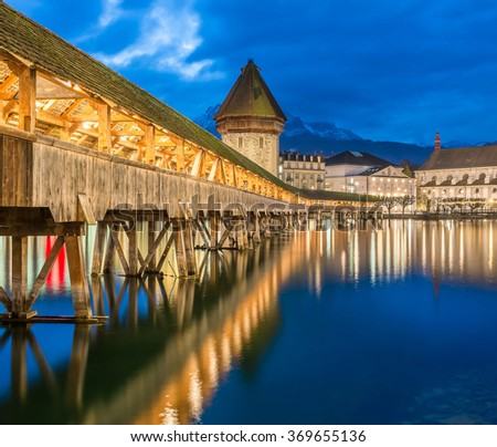 Kapellbrucke Panorama night view Historic Chapel bridge (Famous covered wooden footbridge), Water Tower and Jesuitenkirche over Reuss river Cityscape old town under Dramatic Blue Sky, Switzerland