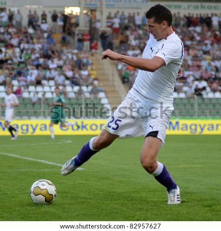 KAPOSVAR, HUNGARY - AUGUST 14: Gabor Dvorchak in action at a Hungarian National Championship soccer game - Kaposvar (green) vs Ujpest (white) on August 14, 2011 in Kaposvar, Hungary. - stock photo