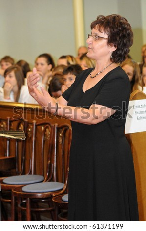 KAPOSVAR, HUNGARY - AUGUST 26: Judit Majnay conducts at the IV. Pannonia Cantat Youth Choir Festival August 26, 2010 in Kaposvar, Hungary - stock photo