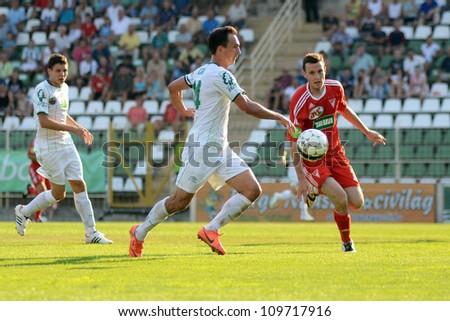 KAPOSVAR, HUNGARY - AUGUST 4: Lorant Olah (white 14) in action at a Hungarian National Championship soccer game Kaposvar (white) vs Debrecen (red) August 4, 2012 in Kaposvar, Hungary. - stock photo