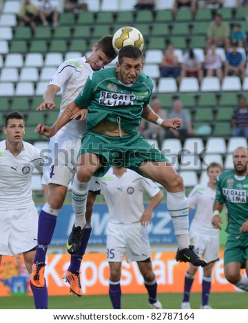 KAPOSVAR, HUNGARY - AUGUST 14: Szabolcs Uveges (in white 4) in action at a Hungarian National Championship soccer game - Kaposvar (green) vs Ujpest (white) on August 14, 2011 in Kaposvar, Hungary. - stock photo
