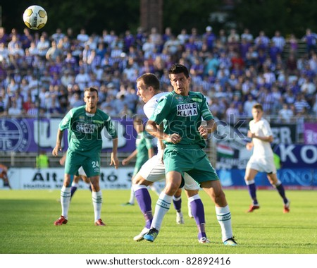 KAPOSVAR, HUNGARY - AUGUST 14: Unidentified players in action at a Hungarian National Championship soccer game - Kaposvar (green) vs Ujpest (white) on August 14, 2011 in Kaposvar, Hungary. - stock photo