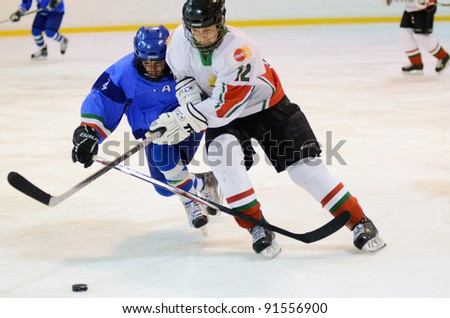 KAPOSVAR, HUNGARY - DECEMBER 17: Unidentified players in action at a friendly ice hockey match with Hungarian (white) and Italian (blue) Under 16 National Team, December 17, 2011 in Kaposvar, Hungary. - stock photo