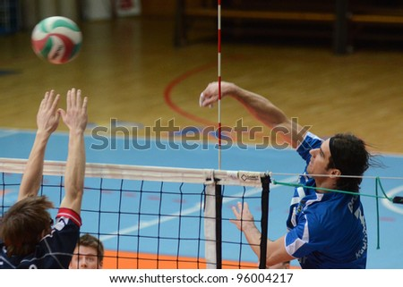 KAPOSVAR, HUNGARY - FEBRUARY 23: Andras Geiger (L) in action at a Hungarian volleyball National Championship game Kaposvar (blue) vs. Csepel (deep blue), on February 23, 2012 in Kaposvar, Hungary. - stock photo