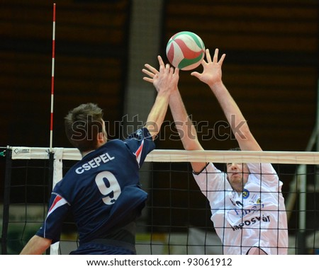 KAPOSVAR, HUNGARY - JANUARY 15: Karoly Lesznyik (in white) in action at a Hungarian volleyball National Championship game Kaposvar (white) vs. Csepel (blue), on January 15, 2012 in Kaposvar, Hungary.