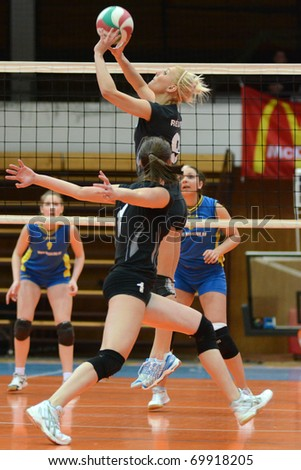 KAPOSVAR, HUNGARY - JANUARY 23: Redei (in the top) posts the ball at the Hungarian NB I. League woman volleyball game Kaposvar vs Miskolc, January 23, 2011 in Kaposvar, Hungary. - stock photo