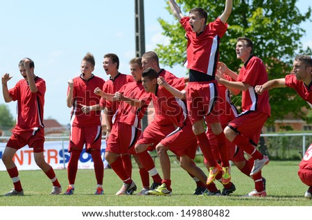 KAPOSVAR, HUNGARY - JULY 20: Nagybajom players in action at the IX. Youth Football Festival match Nagybajom (red) (HUN) vs. Liceul Sportiv (black) (MDA) on July 20, 2013 in Kaposvar, Hungary - stock photo