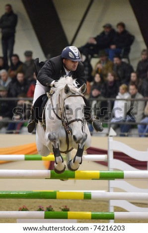 KAPOSVAR, HUNGARY - MARCH 27Attila Szasz jumps with his horse (Venusz) on the Masters Tournament International Jumping Competition, March 27, 2011 in Kaposvar, Hungary - stock photo